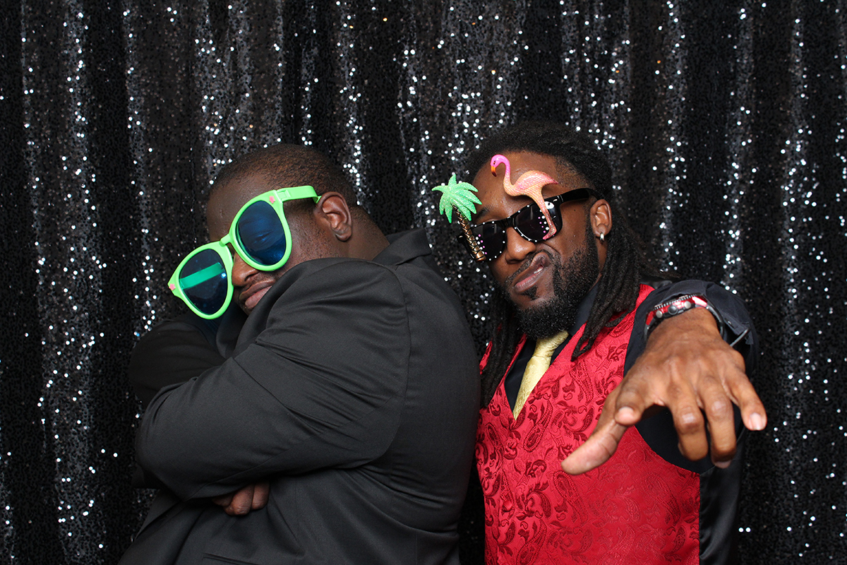 Couple posing on black backdrop with glasses at Jacksonville Photo Booth Rental.