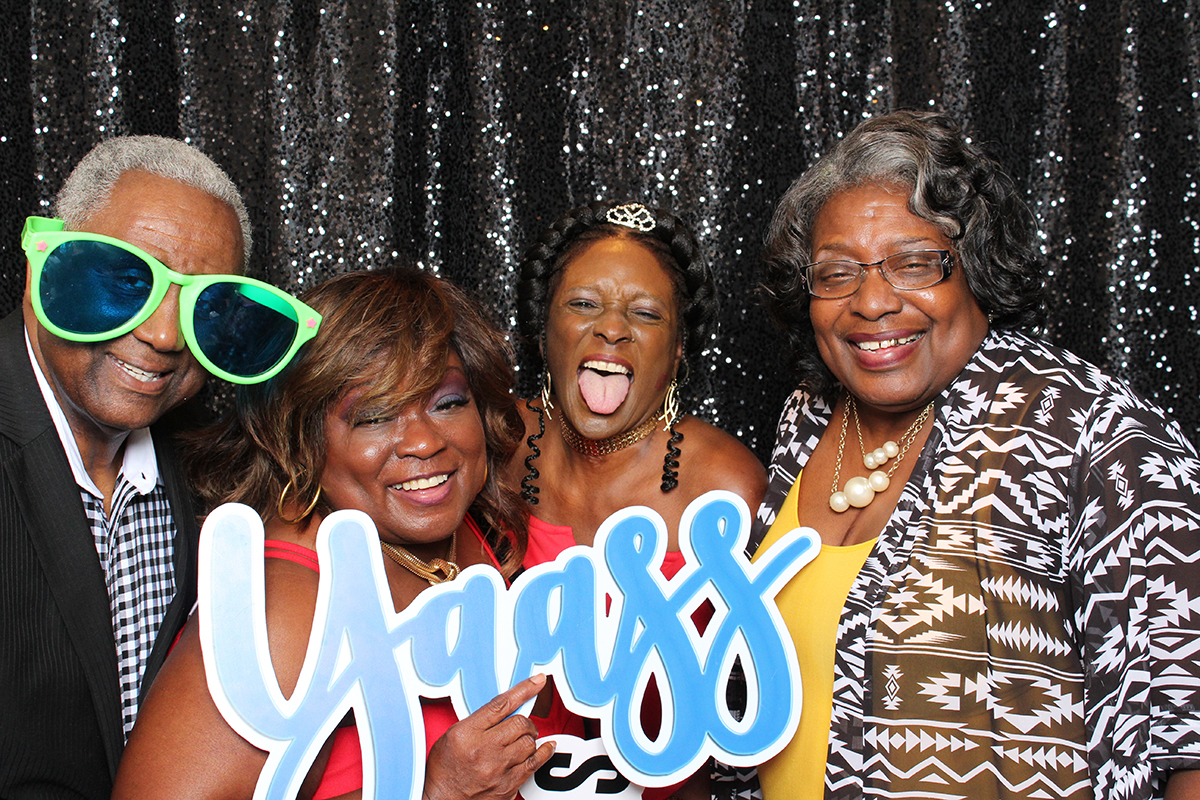 Family posing with a Yass sign on black backdrop at Jacksonville Photo Booth Rental.