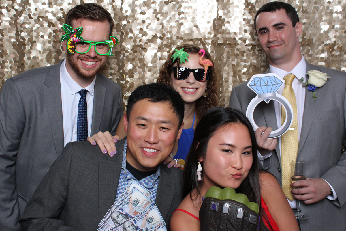 Wedding guests posing with props on gold backdrop at Jacksonville Photo Booth Rental.