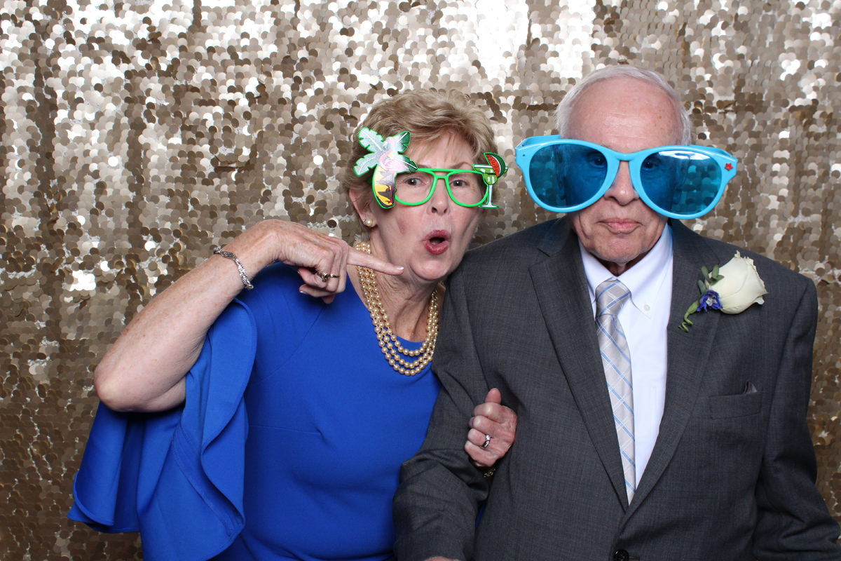 Older couple posing in glasses with gold backdrop at Jacksonville Photo Booth Rental.