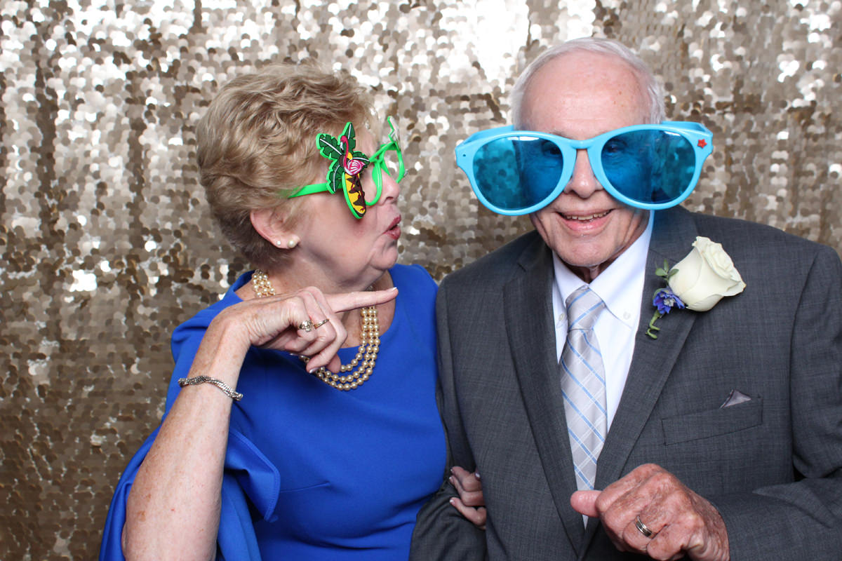 Older couple funny pose on gold backdrop at Jacksonville Photo Booth Rental.