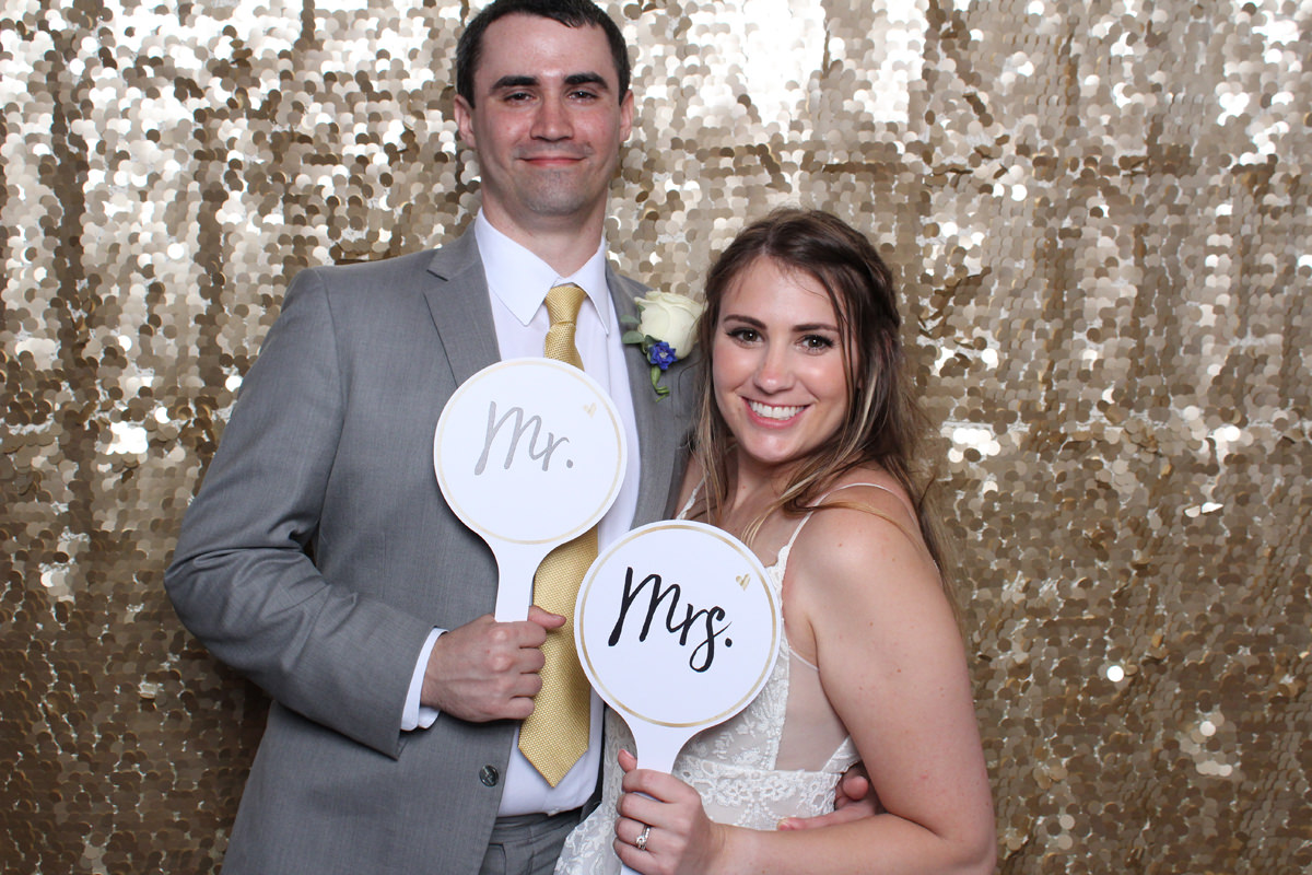 Bride and groom pose with mr and mrs signs on gold backdrop at Jacksonville Photo Booth Rental.