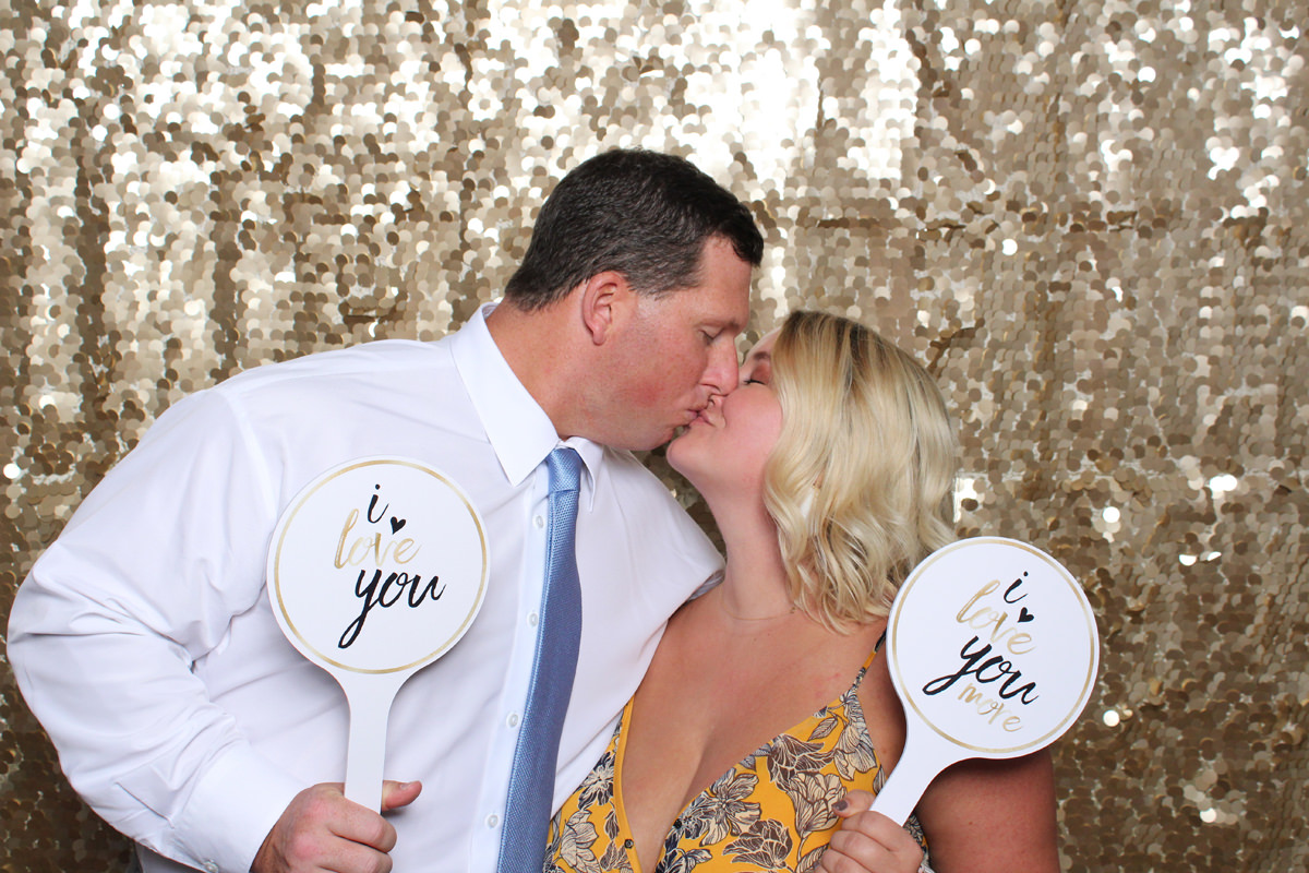 Couple kissing in front of gold backdrop at Jacksonville Photo Booth Rental.