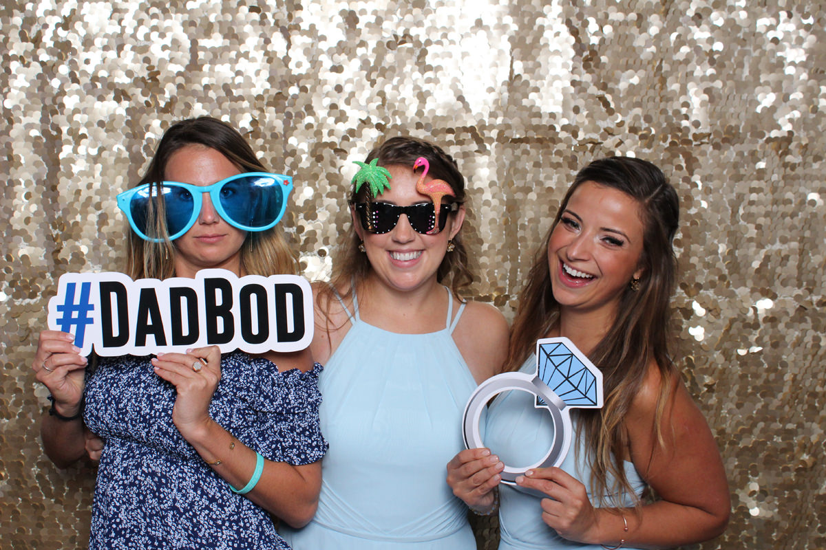 Bridesmaids posing in front of gold backdrop with props at Jacksonville Photo Booth Rental.
