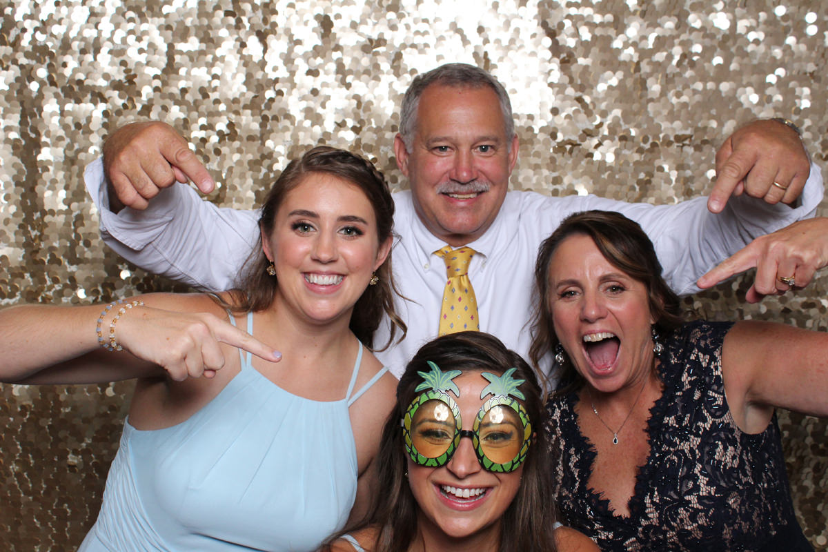 Family posing in booth with gold backdrop at Jacksonville Photo Booth Rental.