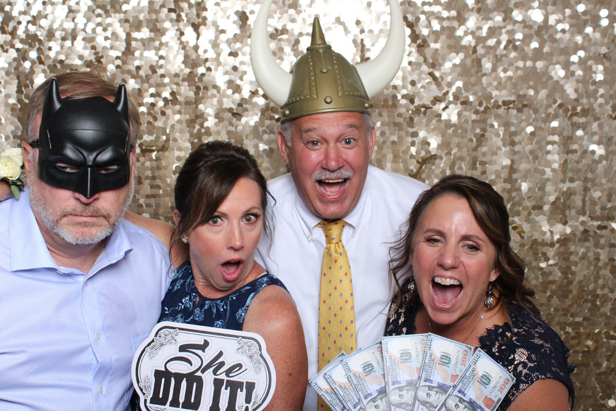 Adults with funny hats and money sign at Jacksonville Photo Booth Rental.