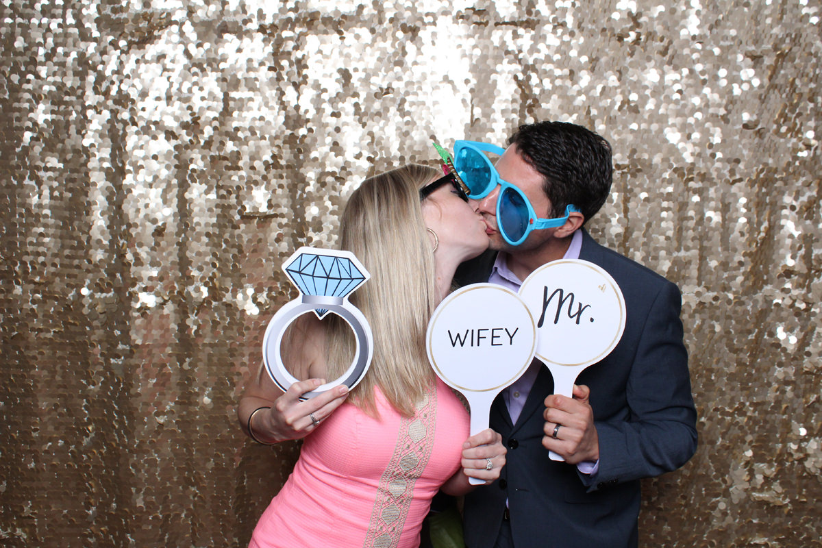 Couple kissing with props in front of gold backdrop at Jacksonville Photo Booth Rental.