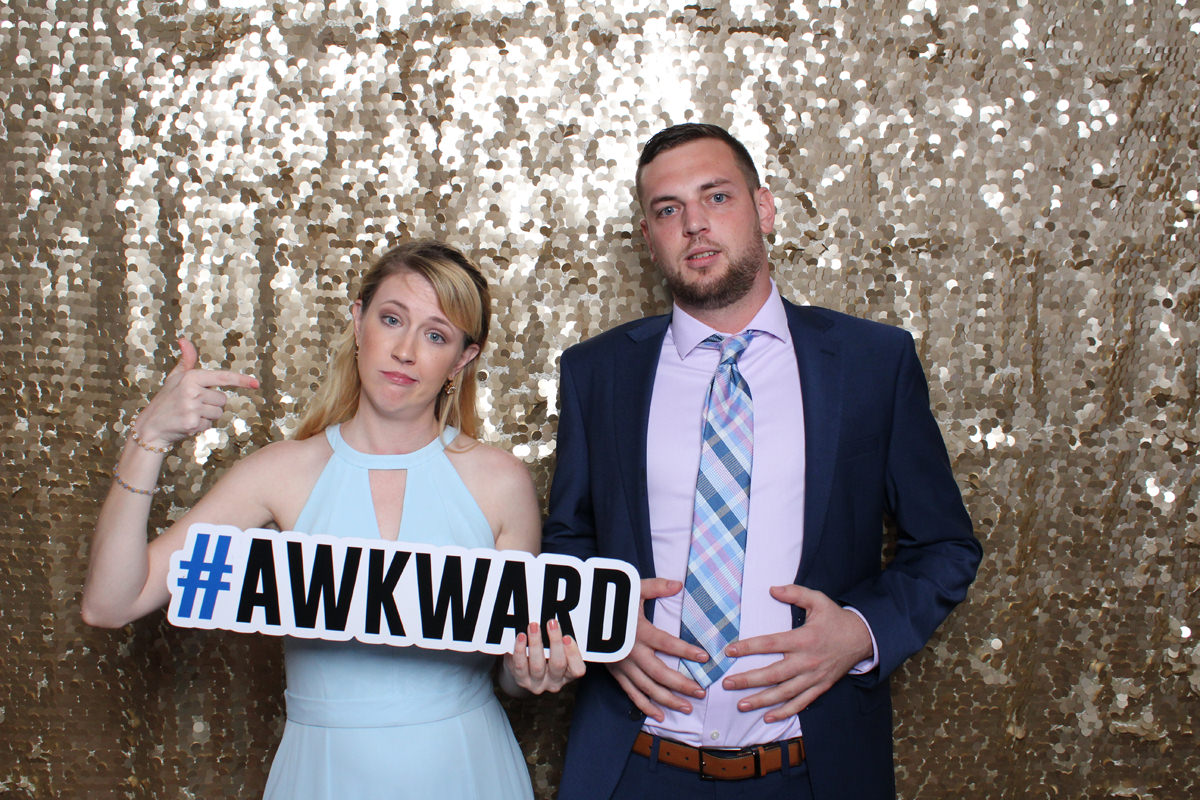 Awkward sign in front of gold backdrop at Jacksonville Photo Booth Rental.
